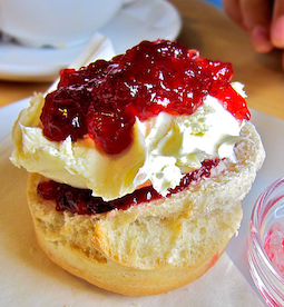 A scone with jam and cream and even more jam